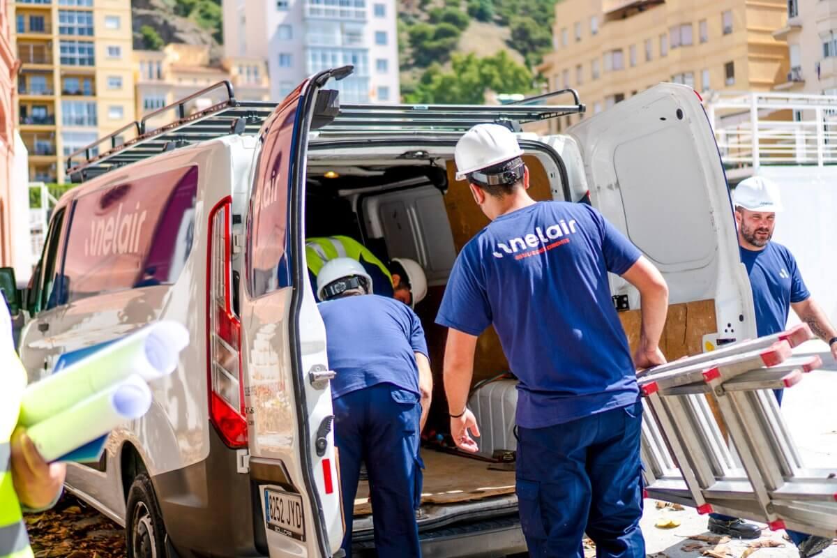 Imagen de trabajadores de Anelair descargando un sistema de climatización en Málaga